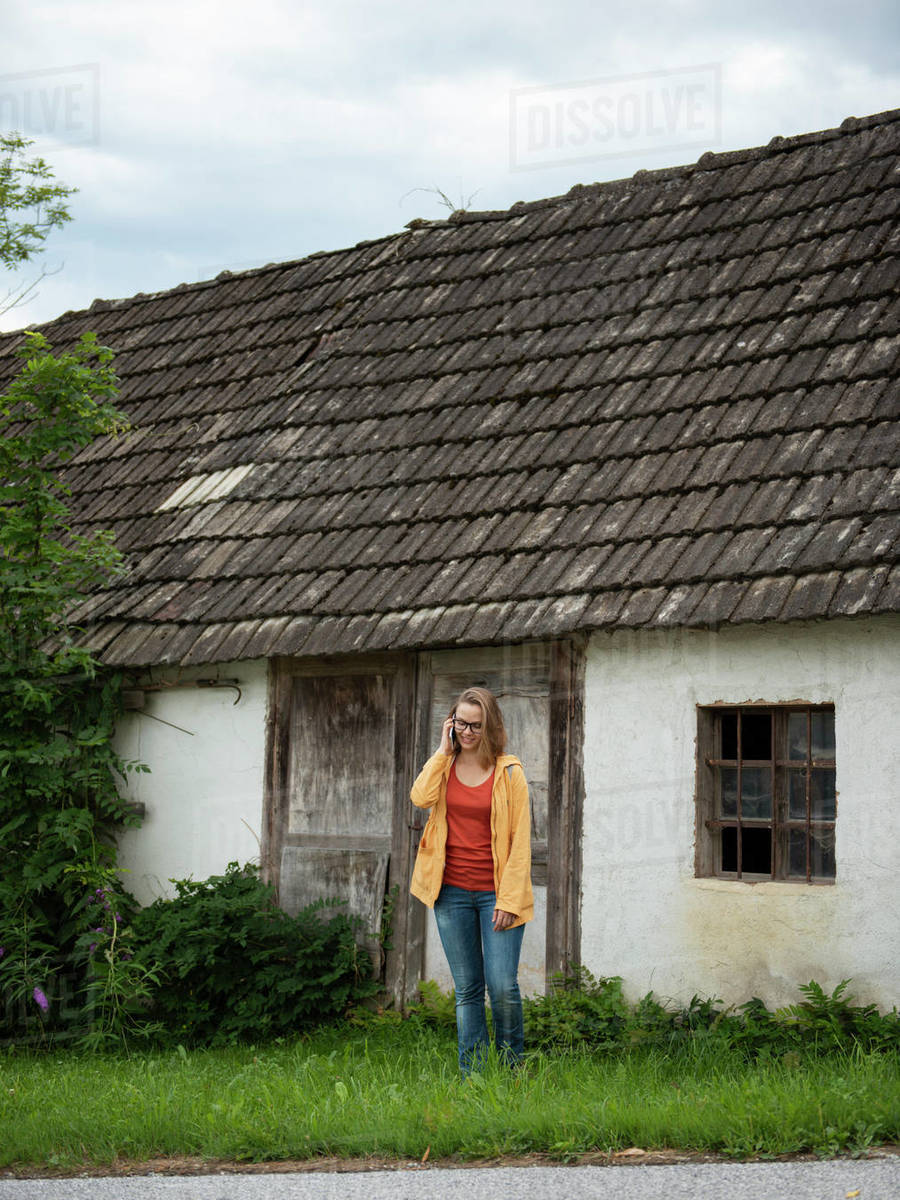 Woman standing near old farmhouse talking by cell phone  Royalty-free stock photo