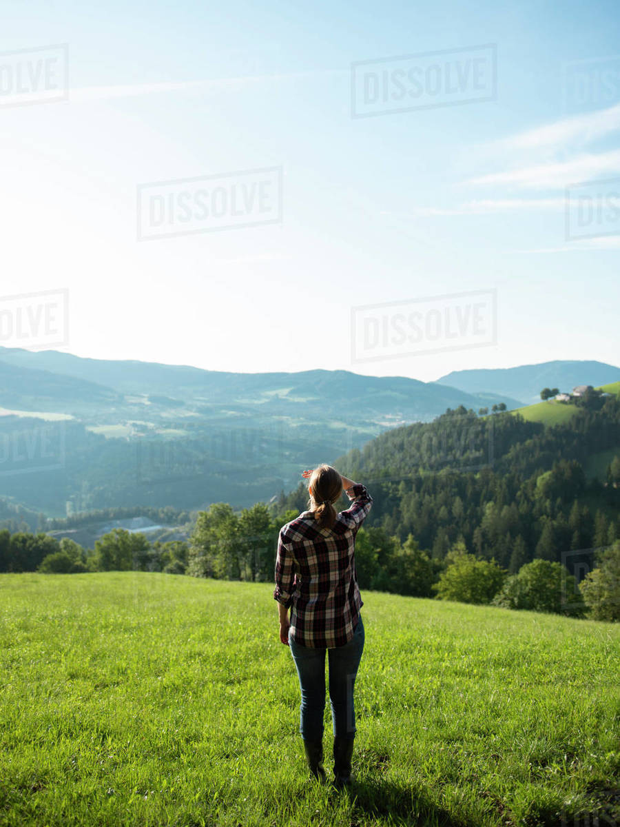 Female farmer standing in grass field covering her eyes by hand and looking at sun  Royalty-free stock photo