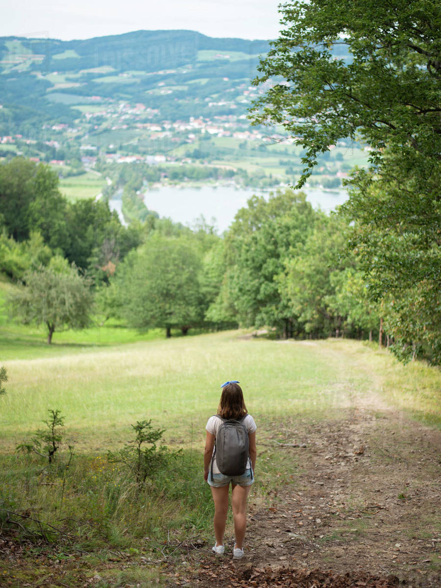 Back view of woman with backpack standing on the hill and enjoying the view Royalty-free stock photo