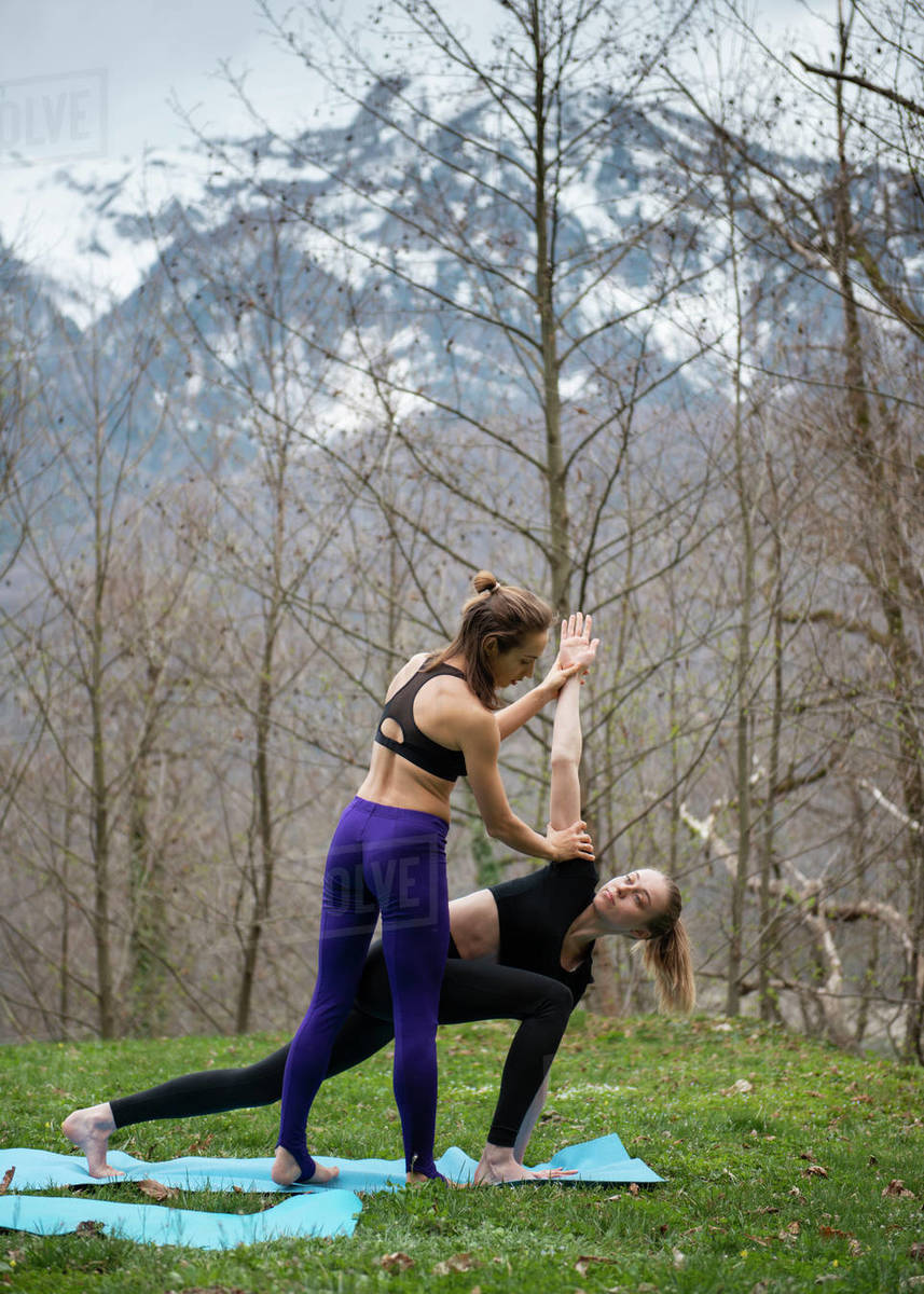 Instructor explaining female how to do yoga pose while training together outdoor on grass against mountains Royalty-free stock photo