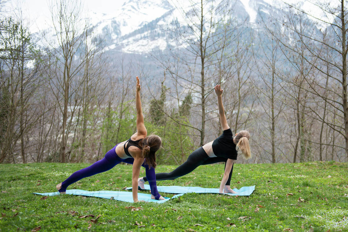Two women practicing yoga together on grass against mountains Royalty-free stock photo