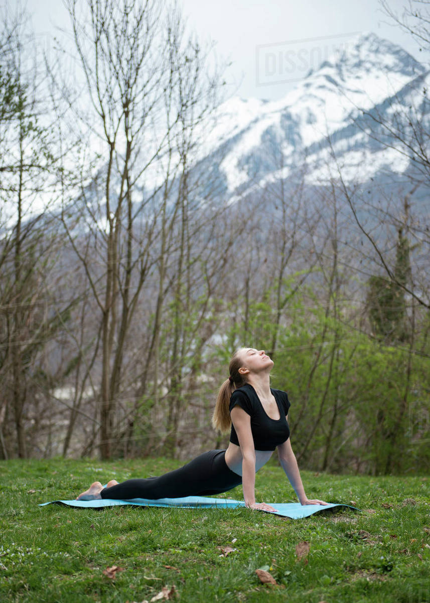 Young woman practicing yoga on grass against mountains Royalty-free stock photo