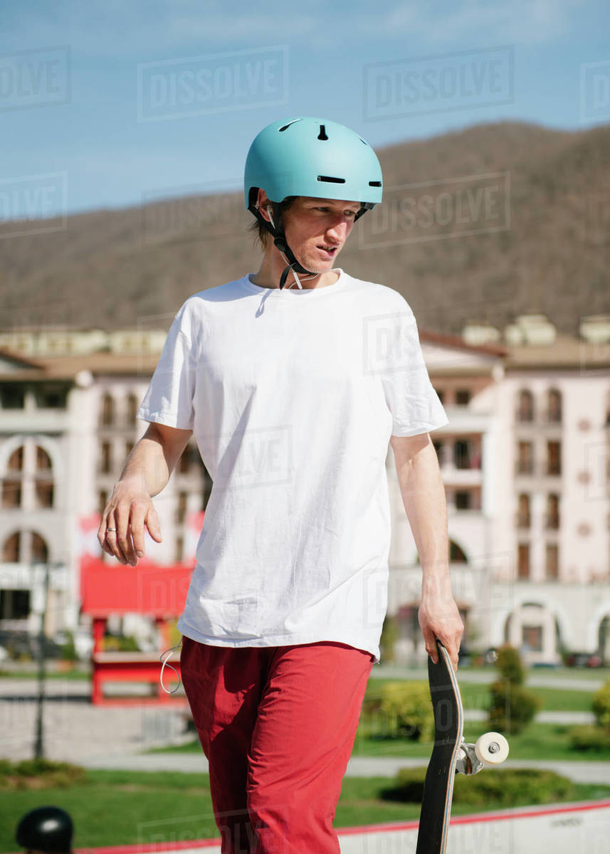 Young man carrying skateboard looking away Royalty-free stock photo