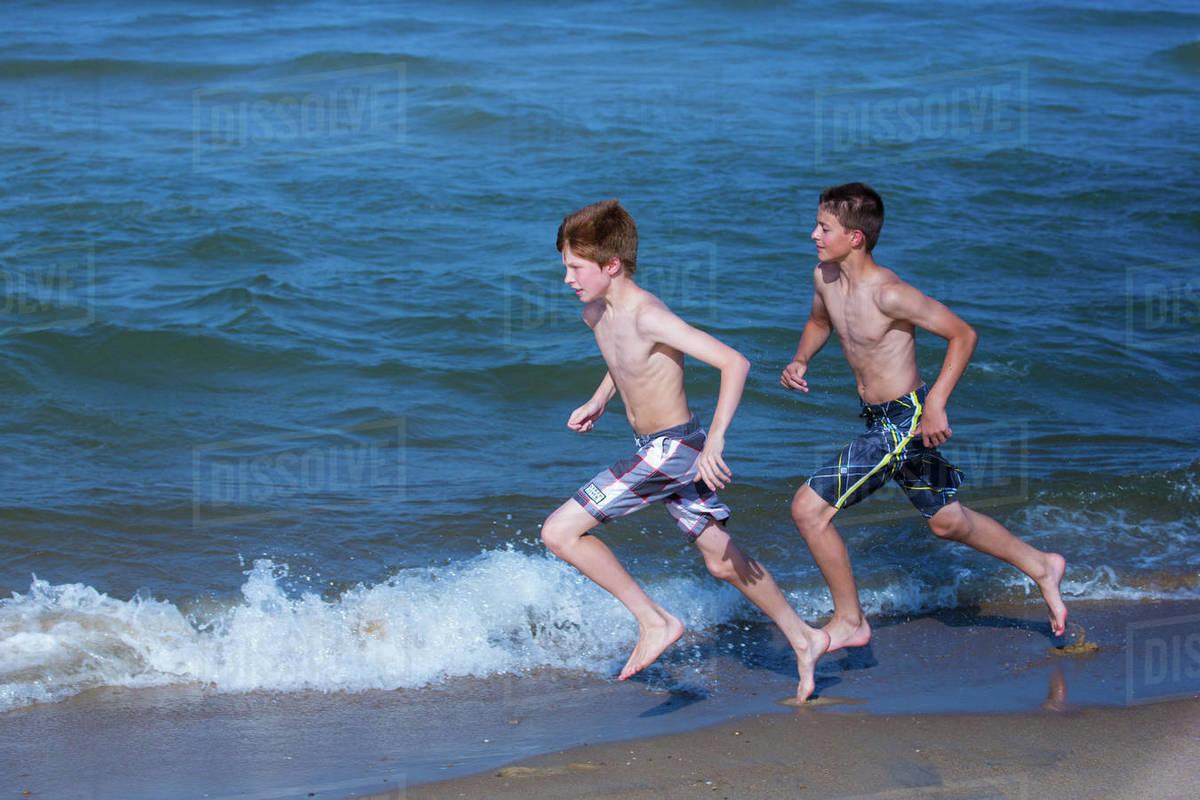 Two boys running along beach - Stock Photo - Dissolve