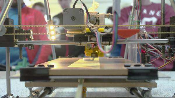 Front look at 3D printer with students in background looking at the printer Royalty-free stock video