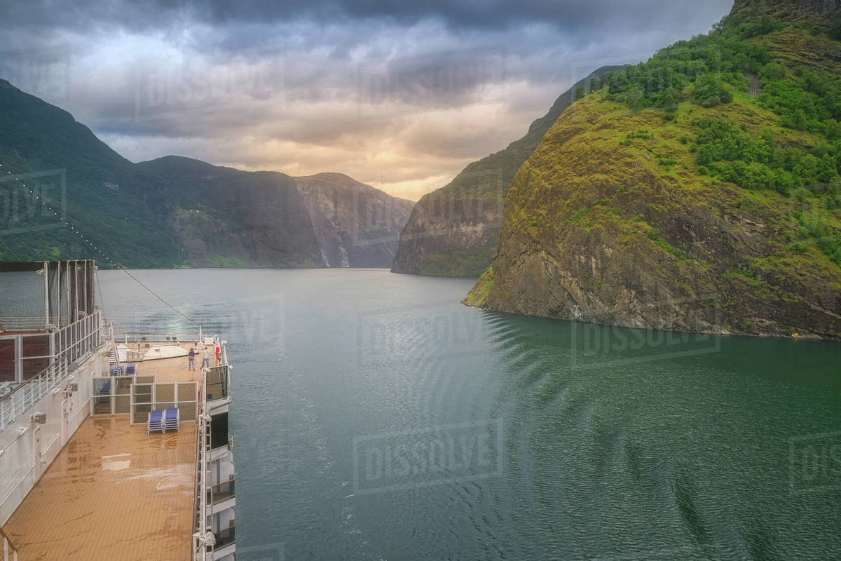 Big fast boat swimming in green water along mountains under cloudy sky in Norway Royalty-free stock photo