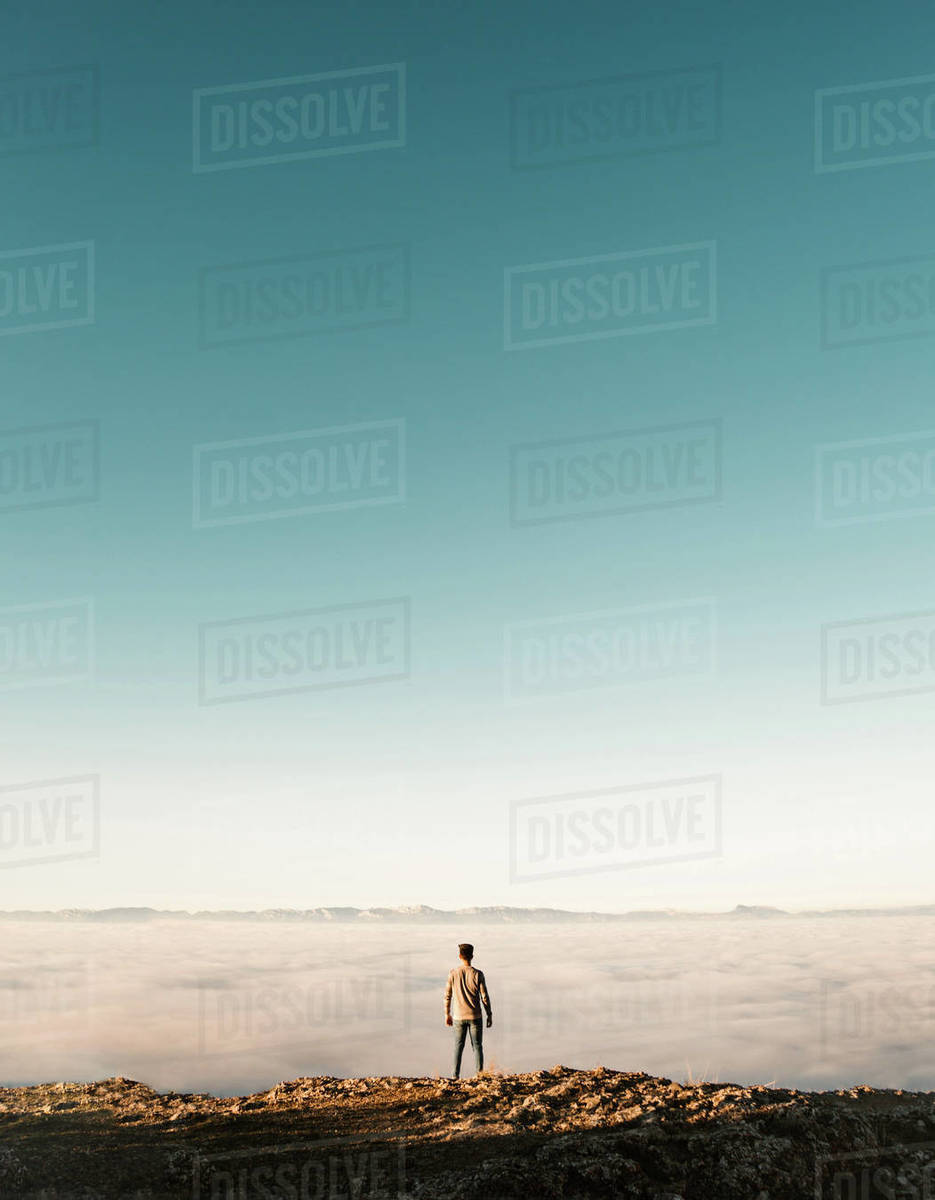 Back view of tourist standing at cliff edge over the clouds. Royalty-free stock photo