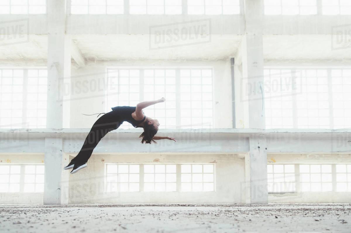 Sportswoman doing flip in urban building Royalty-free stock photo