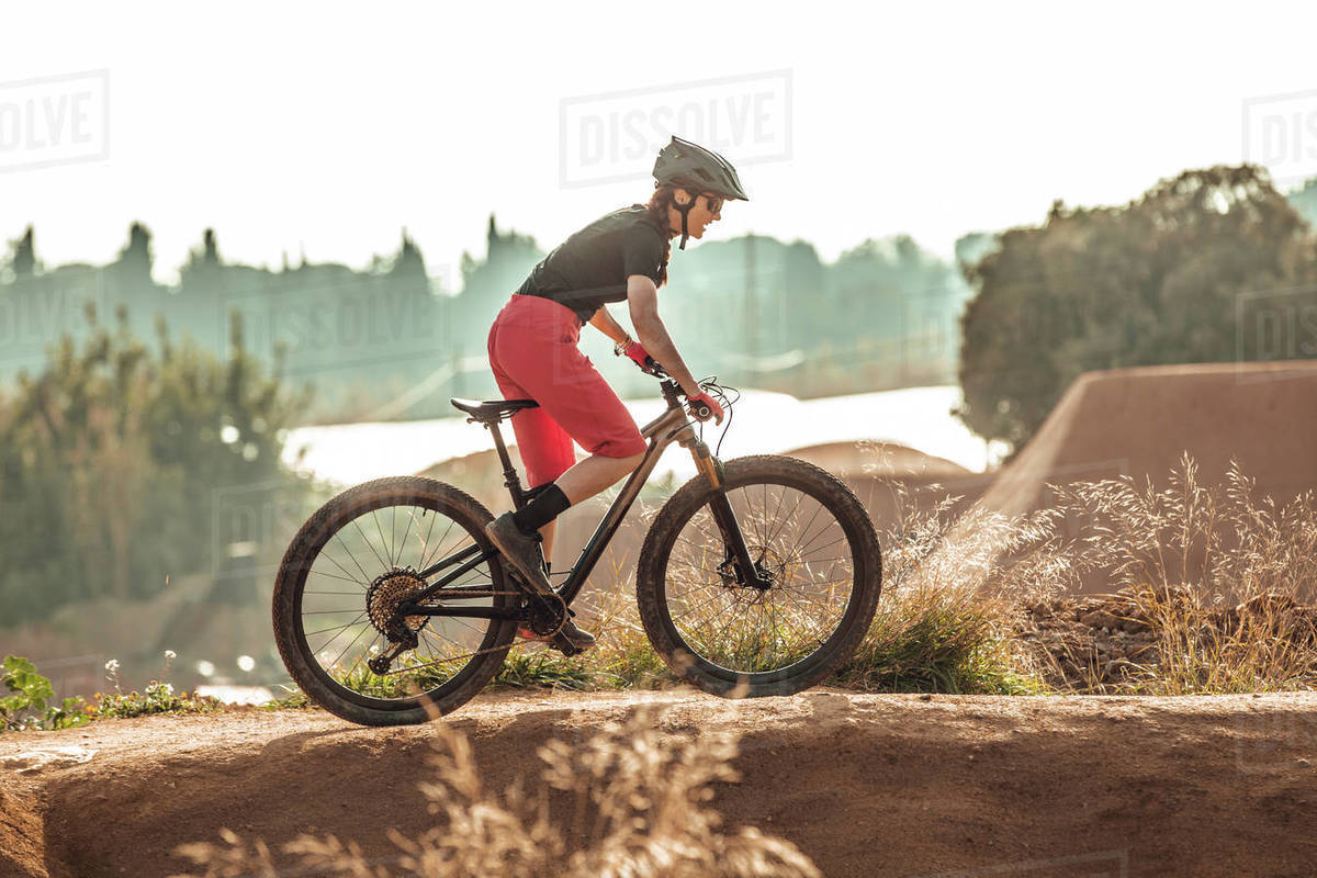 Side view of sportswoman in black helmet and red sportswear with glasses riding mountain bike on training track Royalty-free stock photo