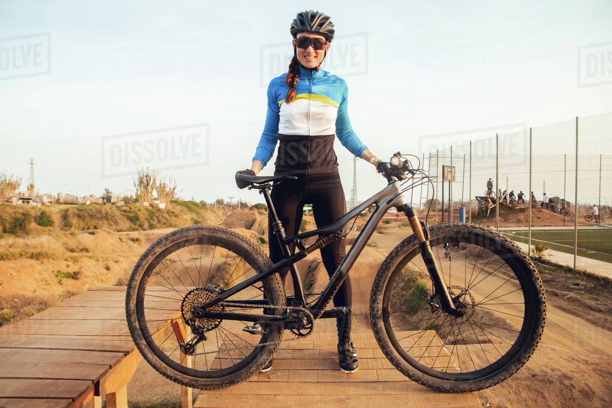 Cheerful young female in sportswear and helmet standing on wooden platform with dusty mountain bike smiling and looking at camera Royalty-free stock photo