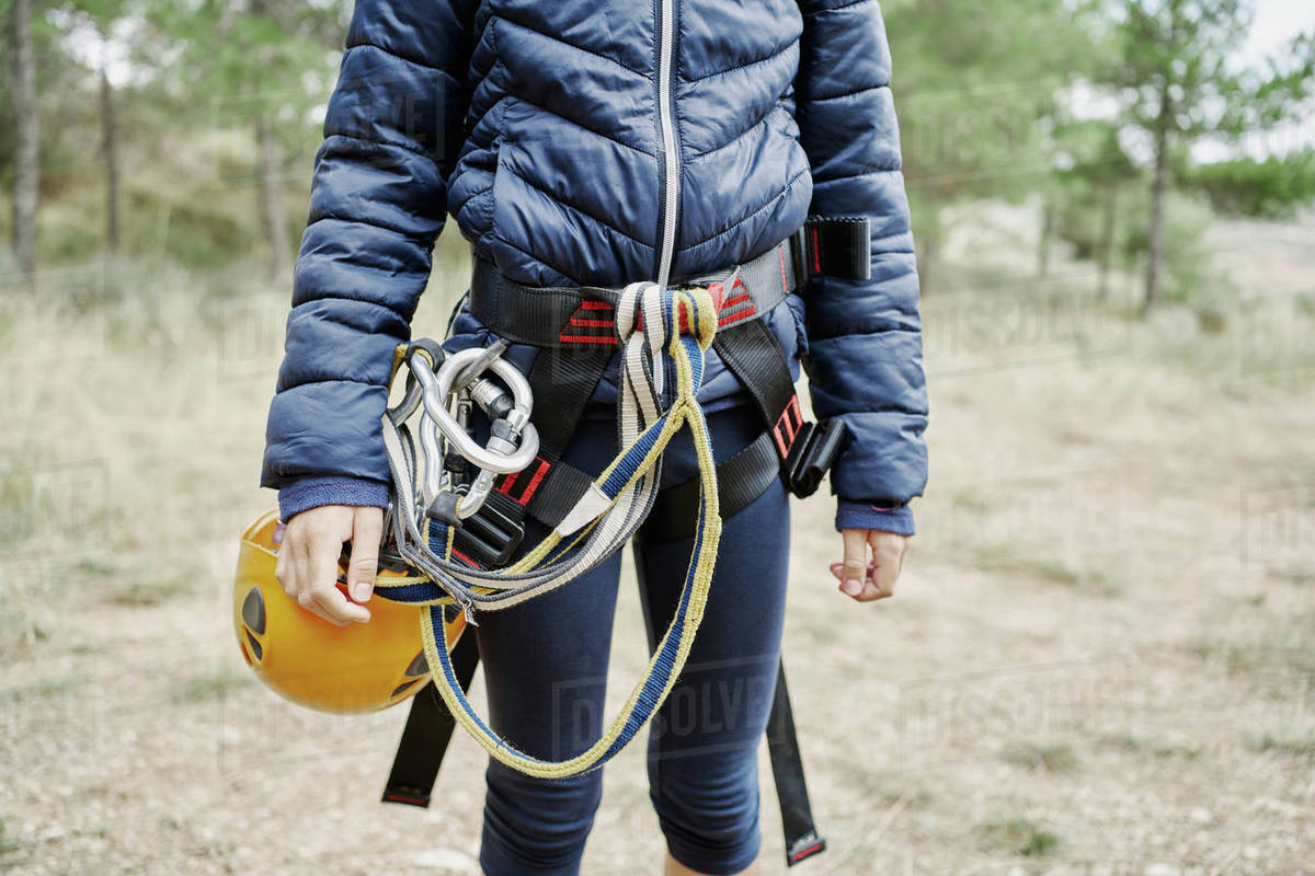 Unrecognizable kid in outerwear wearing safety harness with carabiners and helmet while standing in countryside Royalty-free stock photo