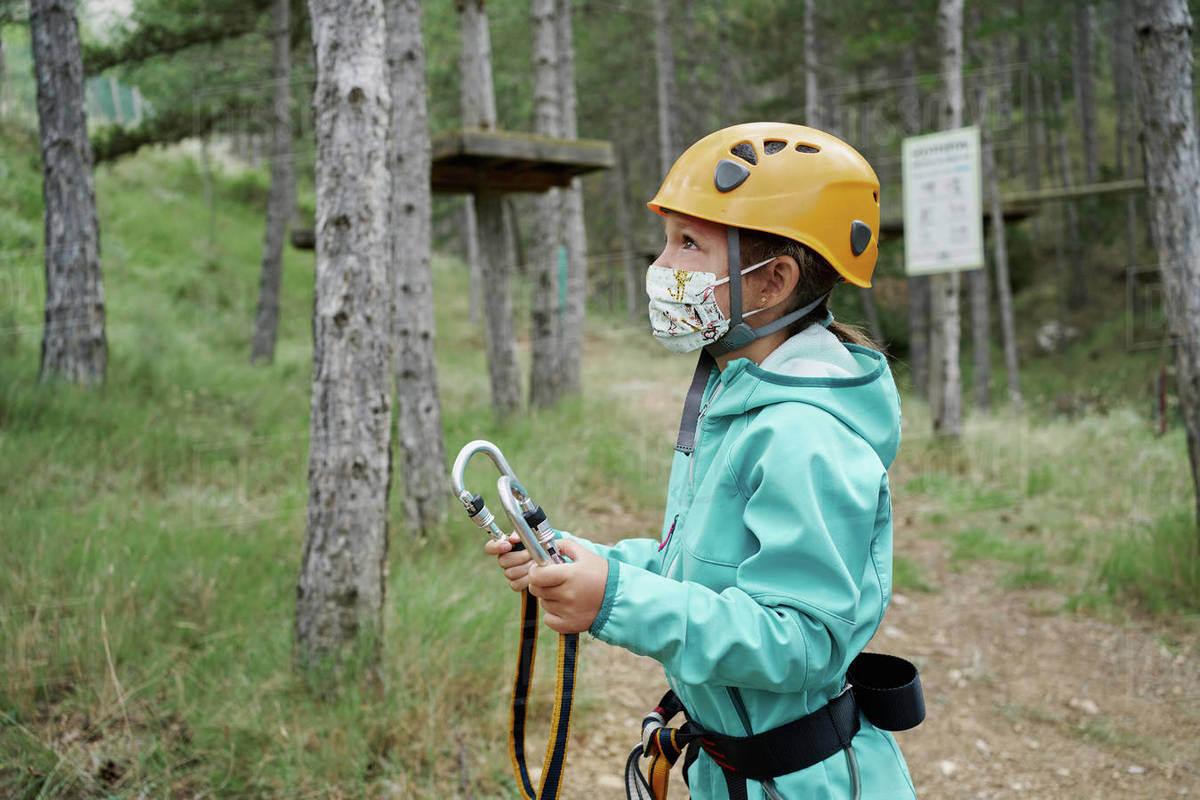 Girl in helmet and fabric mask holding carabiners with ropes and looking away while preparing to climb obstacles in adventure park in forest during pandemic Royalty-free stock photo