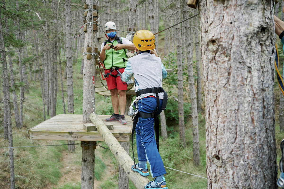 Unrecognizable boy in helmet using safety rope to walk on log towards man while climbing obstacle course in adventure park in forest Royalty-free stock photo