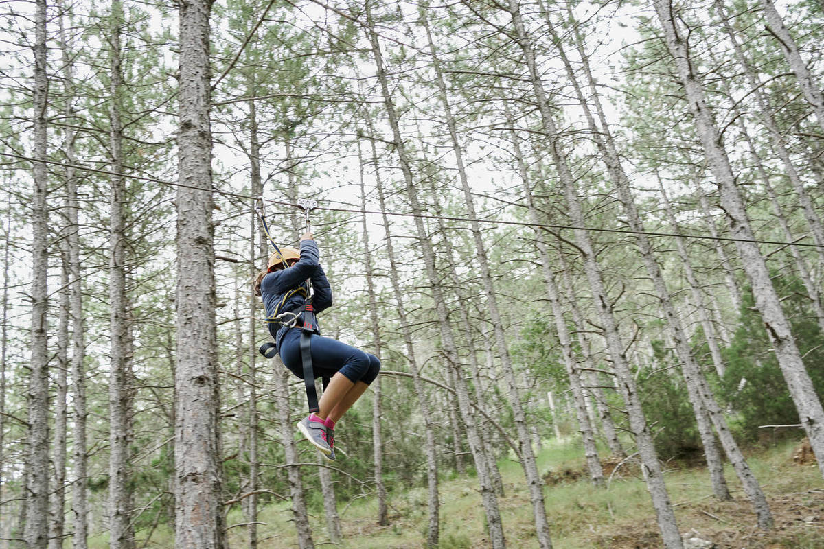 From below female climber in mask and helmet suing harness to ride rope course in adventure park in forest during pandemic Royalty-free stock photo