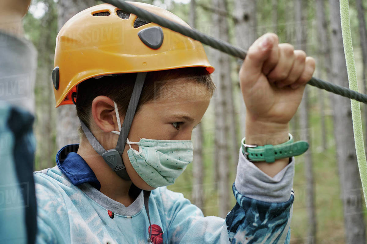 Boy in helmet and face mask grasping rope while climbing obstacle course in adventure park in forest during pandemic Royalty-free stock photo