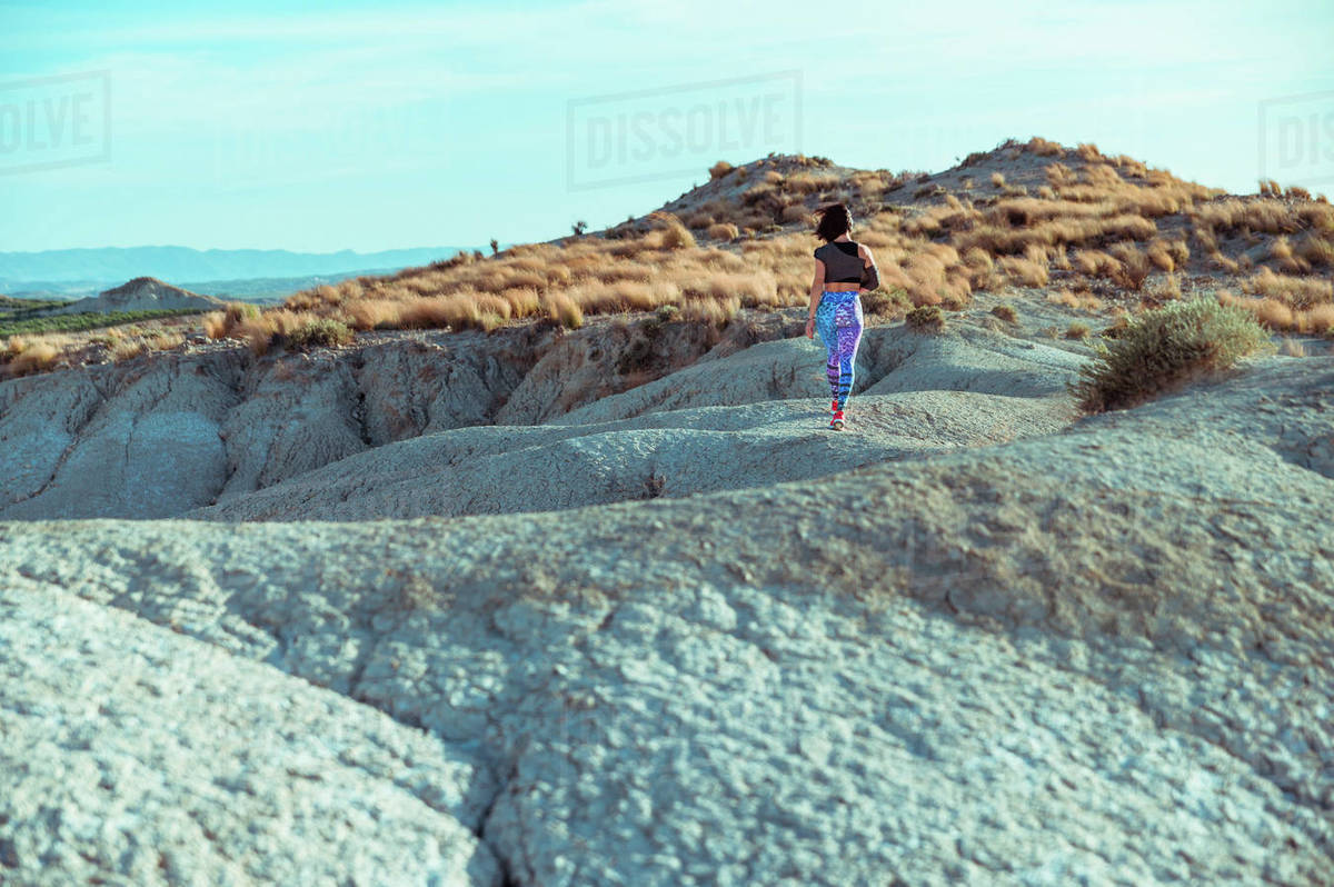 Back view of unrecognizable active female athlete in sportswear walking on rocky slope of rough desert hilly terrain under blue sky Royalty-free stock photo