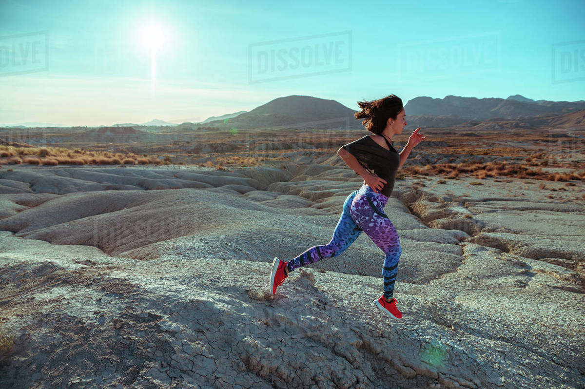 Full body side view of active female athlete in sportswear running and jumping over rocky slope of rough desert hilly terrain under blue sky Royalty-free stock photo