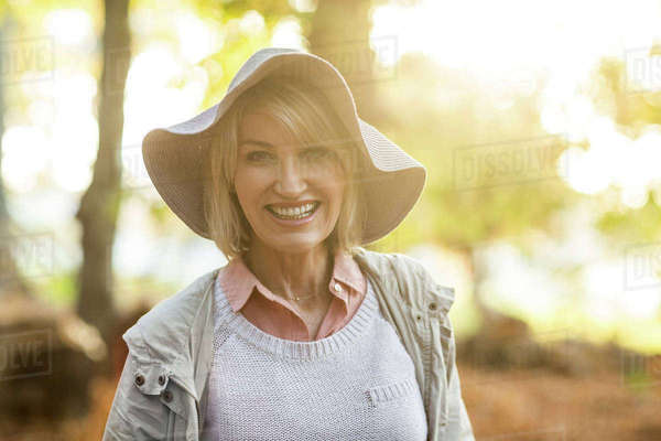 Portrait of cheerful mature woman wearing hat against trees Royalty-free stock photo