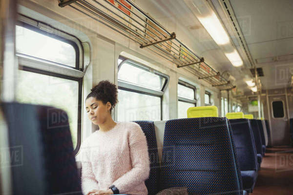 Young woman napping while sitting in train Royalty-free stock photo