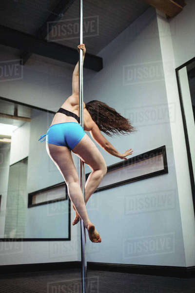 Pole dancer practicing pole dance in fitness studio Royalty-free stock photo
