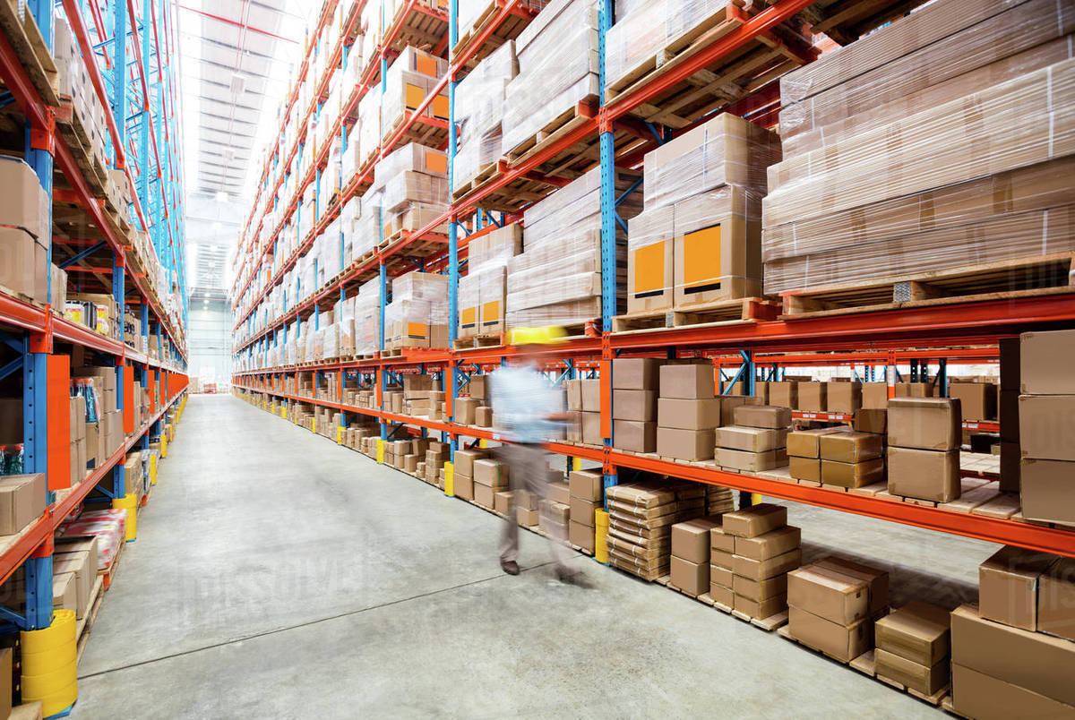 warehouse worker walking in an aisle in warehouse stock photo