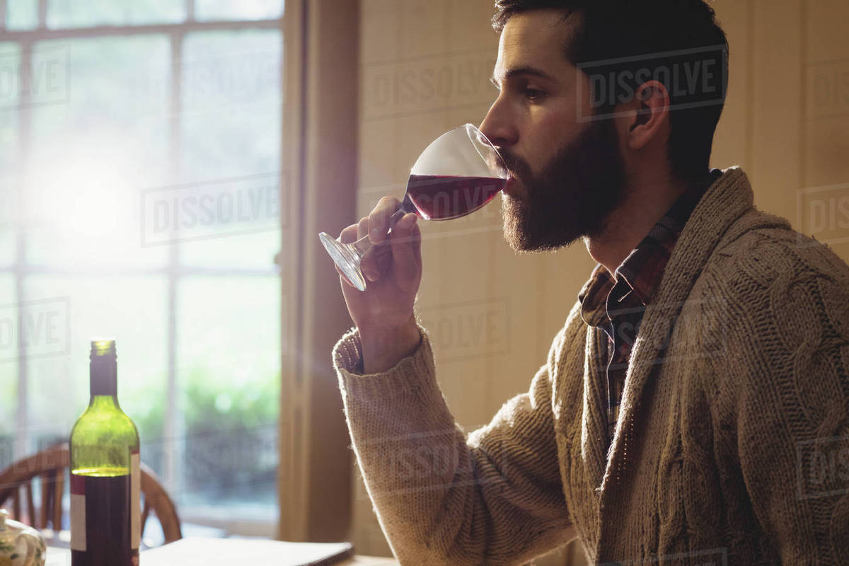cb09bbfc6ed1 Profile view of hipster man drinking glass of wine in country house ...