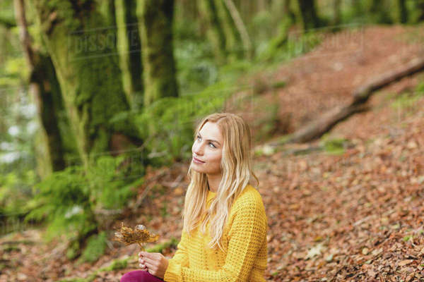 Beautiful blonde woman sitting on the ground in the woods Royalty-free stock photo