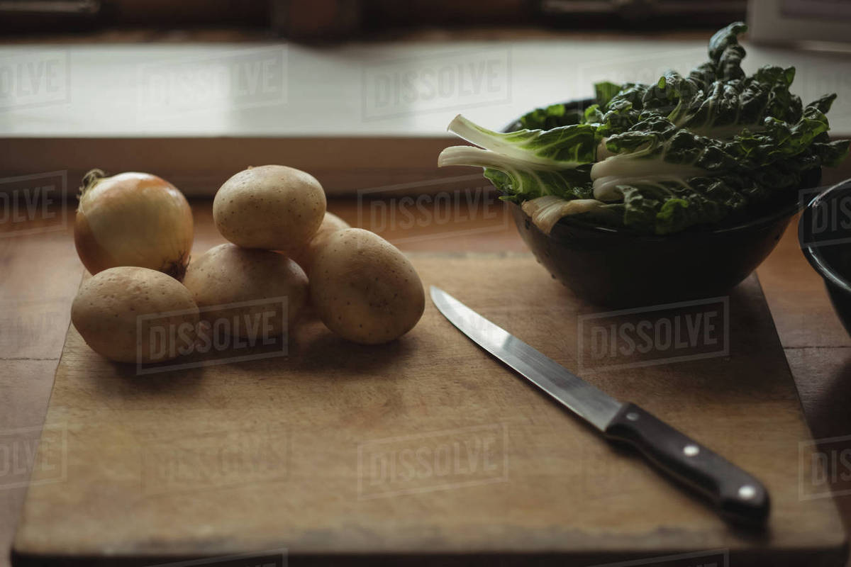Close Up Of Potatoes Onion And Lettuce On Cutting Board With Knife Stock Photo