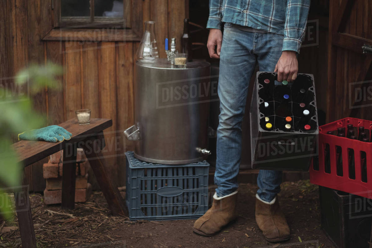 Man carrying homemade beer bottles in a crate at home brewery