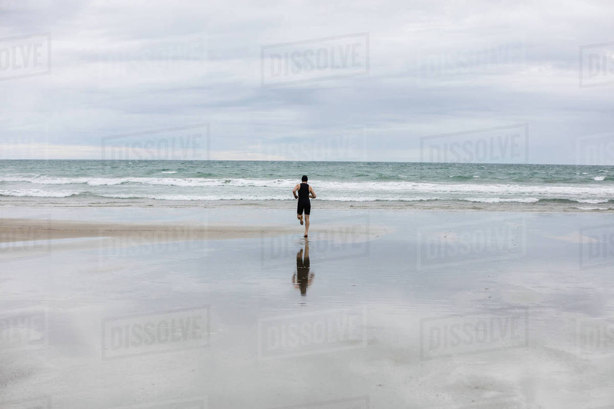 1ede12d93d6 Rear view of man in swimming costume and swimming cap running on beach