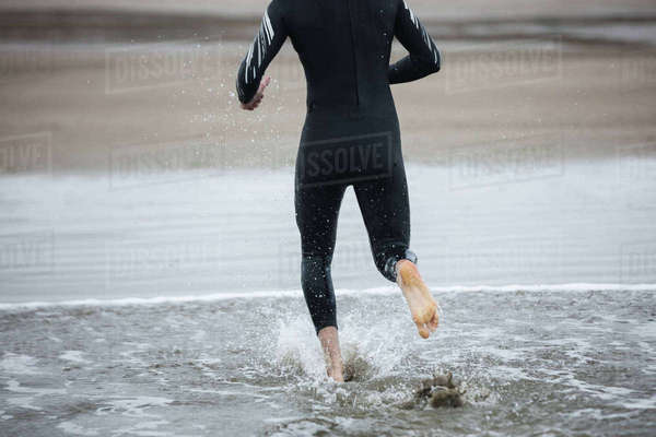 5b89a5d6020 Low section of athlete in wet suit running towards the beach Royalty-free  stock photo
