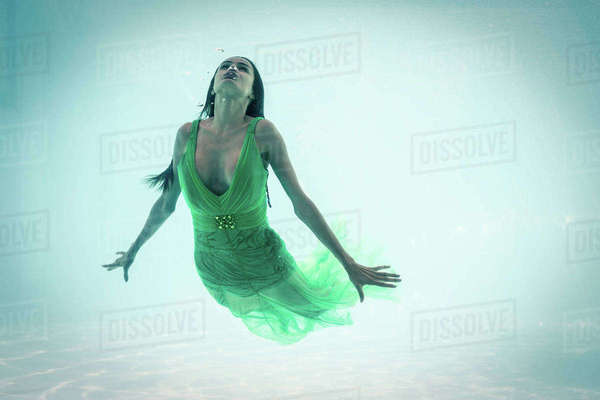 Brunette in evening gown swimming in pool underwater Royalty-free stock photo