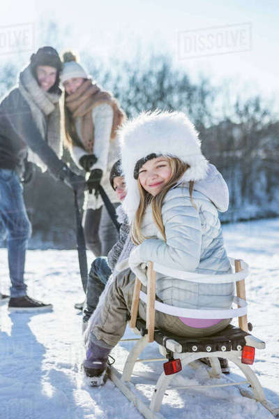 Portrait of family playing with sled on a beautiful snowy day Royalty-free stock photo