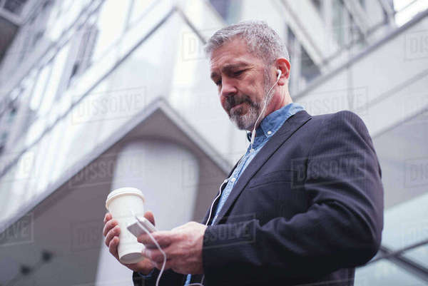 Low angle view of businessman using phone while standing against building Royalty-free stock photo
