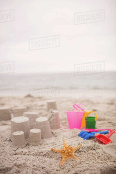 Sandcastle with bucket and spade at beach on a sunny day Royalty-free stock photo