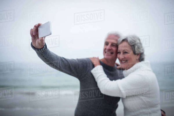 Senior couple taking a selfie on mobile phone at beach Royalty-free stock photo