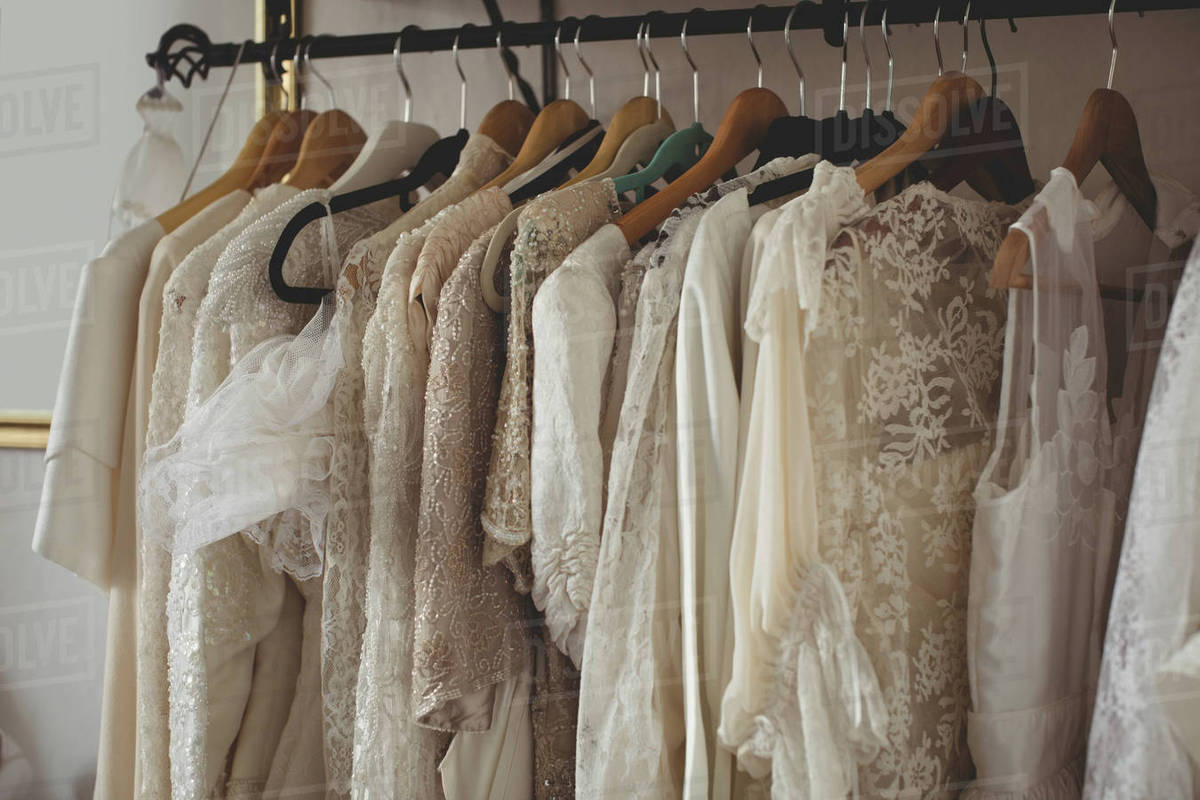 69e464d883 Variety of wedding dresses in wardrobe at boutique stock photo