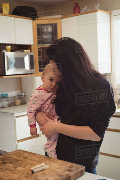 Affectionate mother carrying her baby in kitchen at home Royalty-free stock photo