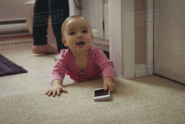 Portrait of smiling baby girl with mobile phone lying on floor at home Royalty-free stock photo