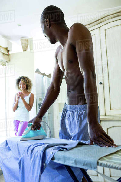 Young man ironing a shirt while woman having coffee in background Royalty-free stock photo