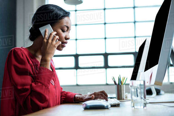 Woman talking on phone while using computer in office Royalty-free stock photo