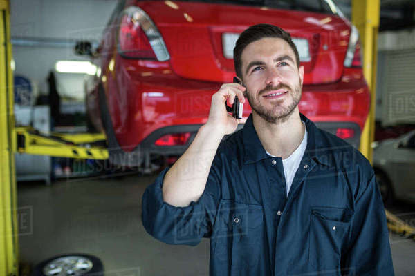 Mechanic talking on a mobile phone at the repair garage Royalty-free stock photo