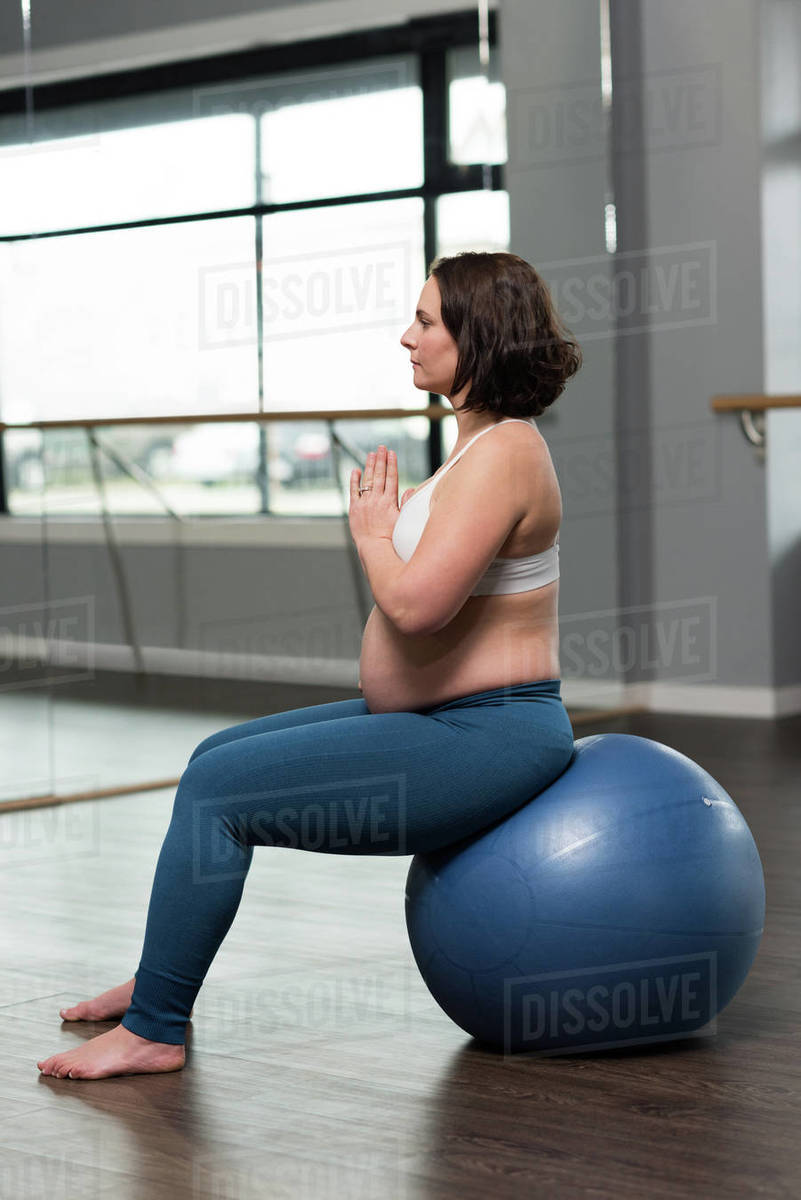Pregnant Woman Performing Yoga On Exercise Ball At Home Stock Photo Dissolve