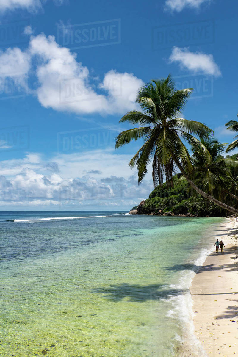 A couple walking along Anse Parnel on the southeast coast of Mahe, Seychelles, Indian Ocean, Africa Royalty-free stock photo