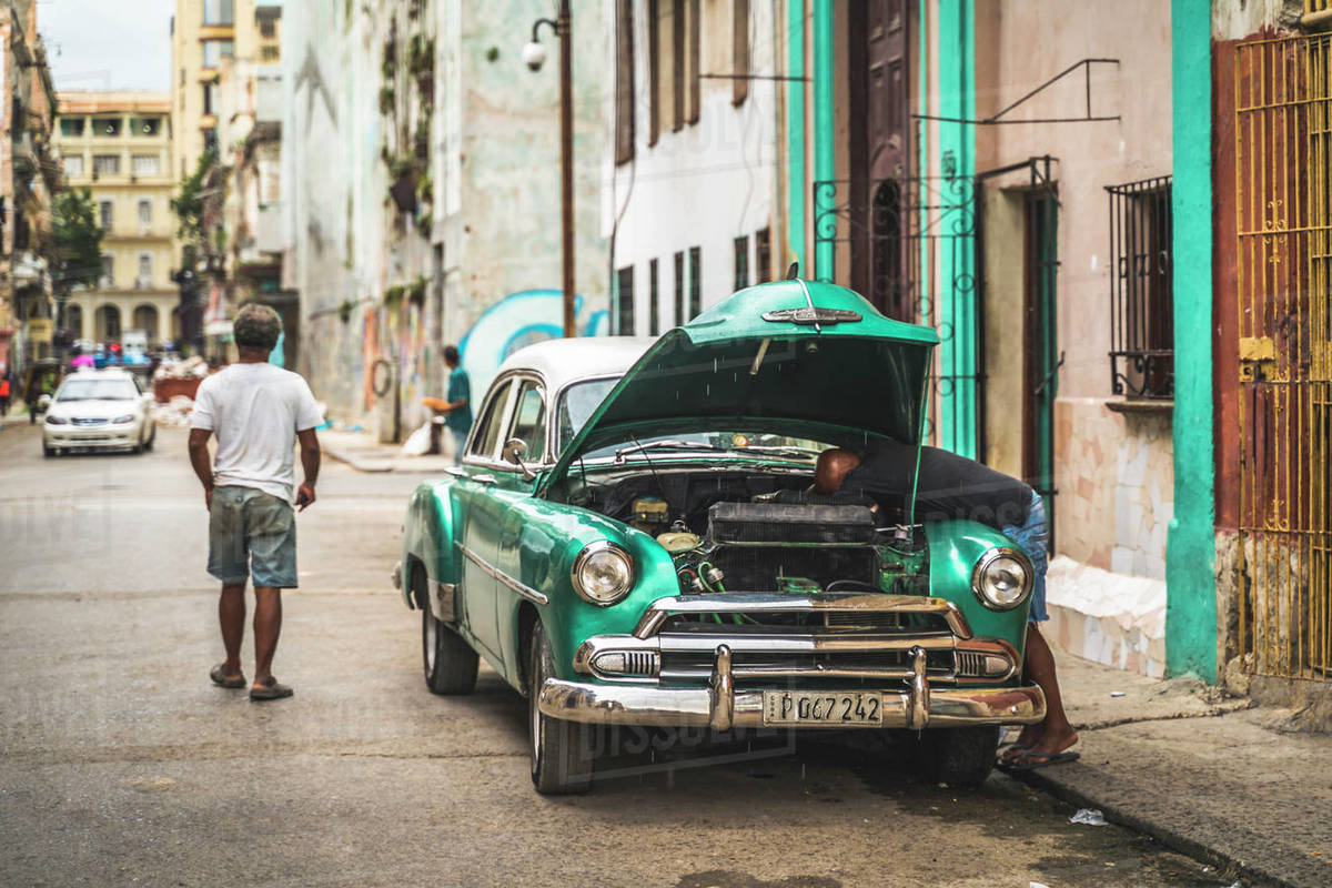 Local fixing his broken down American vintage car, La Habana (Havana), Cuba, West Indies, Caribbean, Central America Royalty-free stock photo