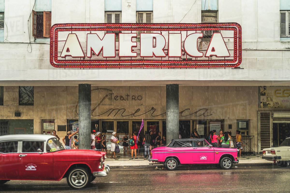Pink and red vintage cars outside Teatro America in rain, La Habana (Havana), Cuba, West Indies, Caribbean, Central America Royalty-free stock photo