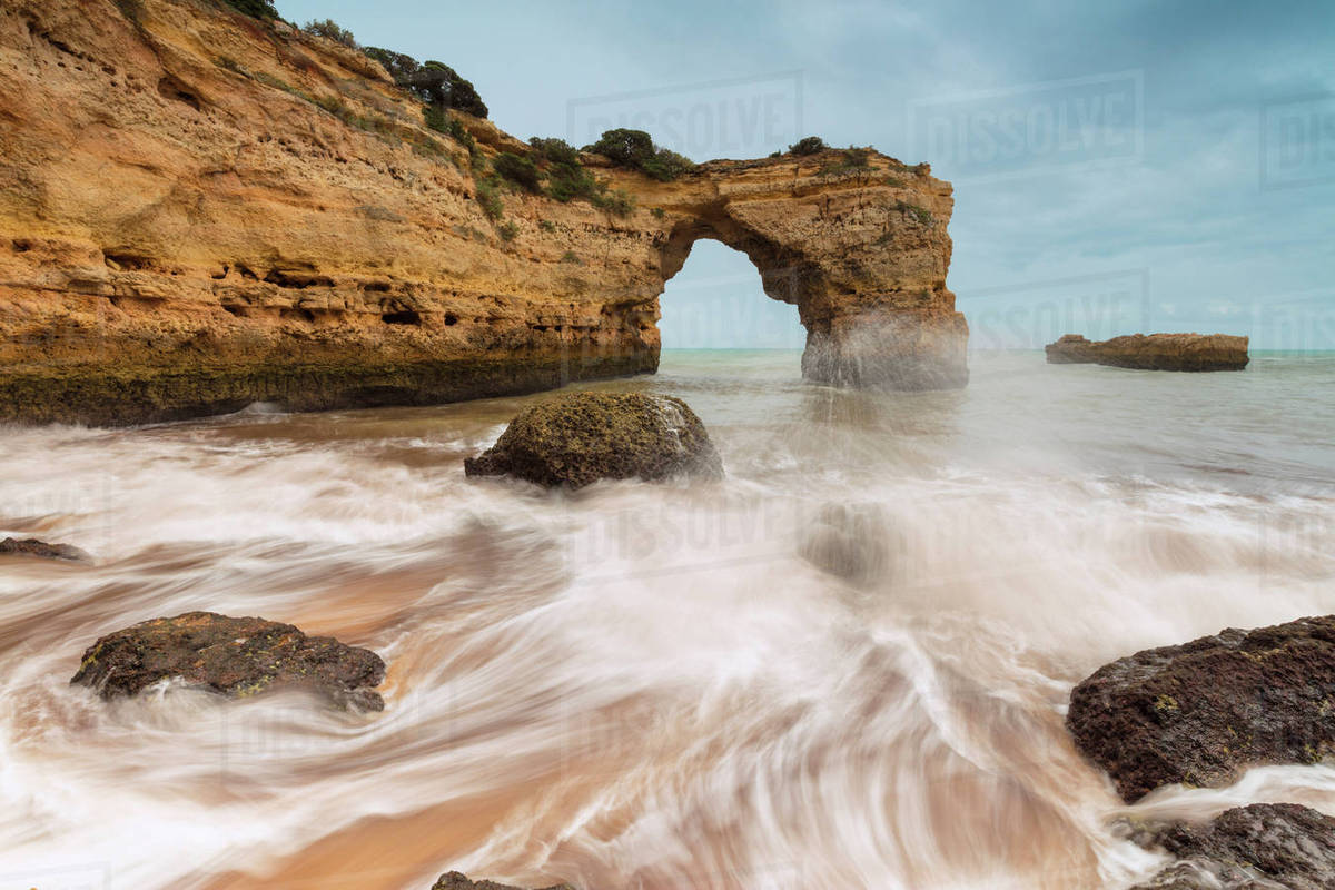 Waves crashing on the sand beach surrounded by cliffs, Albandeira, Lagoa  Municipality, Algarve, Portugal, Europe stock photo
