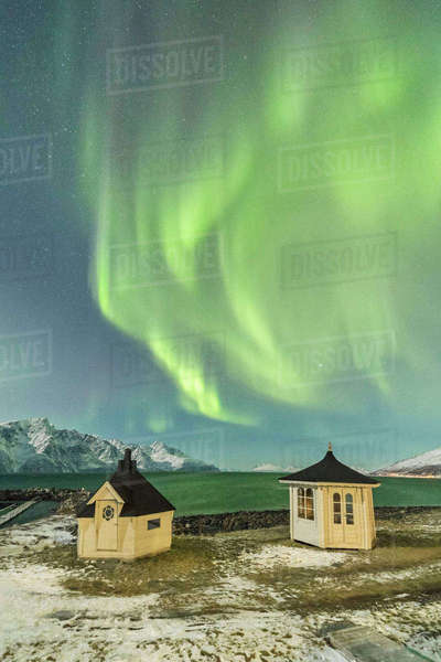 The Northern Lights (aurora borealis) and stars illuminate the wooden huts by icy sea, Djupvik, Lyngen Alps, Troms, Norway, Scandinavia, Europe Royalty-free stock photo