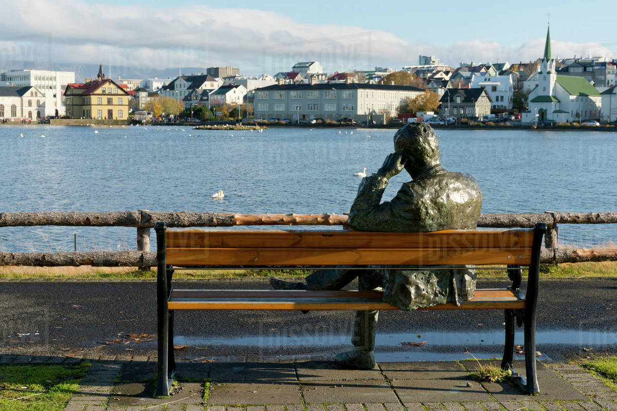 Sculpture Of A Man Sitting On A Park Bench In Front Of Tjornin Lake
