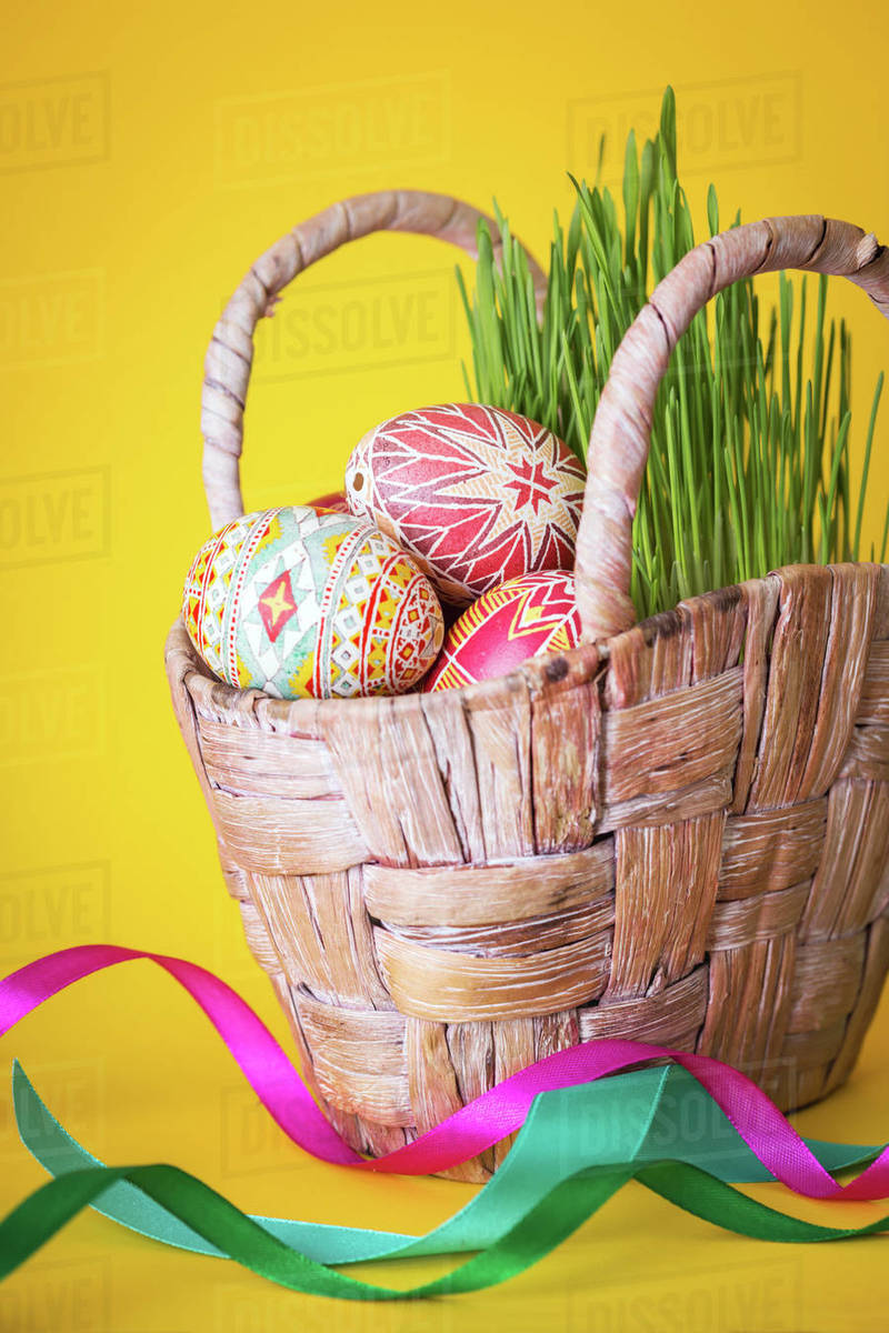 Happy Easter - basket with beautiful Easter egg Pysanka handmade on a yellow background. ukrainian traditional Royalty-free stock photo